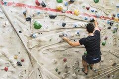 Αναρρίχηση βράχου άσκησης ατόμων στον τεχνητό τοίχο στο εσωτερικό ηθοποιών στοκ φωτογραφία