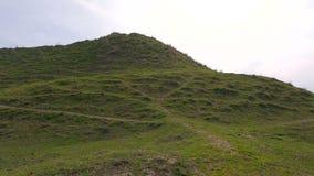 Αναρρίχηση επάνω στον πράσινο λόφο στο νεφελώδη καιρό φιλμ μικρού μήκους