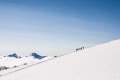 Αναρρίχηση των ορειβατών στη χιονώδη κορυφή βουνών Στοκ φωτογραφία με δικαίωμα ελεύθερης χρήσης