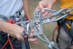 Αναρριμένος στο εργαλείο που συνδέεται με το θηλυκό και αρσενικό λουρί ορειβατών Στοκ Εικόνες