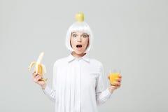 Αναρωτημένη νέα γυναίκα με το μήλο στην επικεφαλής μπανάνα εκμετάλλευσής της Στοκ εικόνα με δικαίωμα ελεύθερης χρήσης