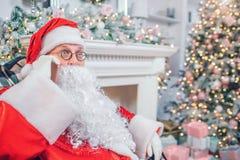 Αναρωτημένος Άγιος Βασίλης κάθεται στο εορταστικό δωμάτιο Μιλά στο τηλέφωνο Ο τύπος είναι κατάπληκτος Είναι μόνος στο δωμάτιο στοκ εικόνες