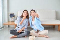 Αναρωτημένος κατάπληκτος εντυπωσιασμένος gesturing δείκτης κοριτσιών που τρώει popcorn που προσέχει το αστείο κωμικό πρόγραμμα με στοκ φωτογραφίες με δικαίωμα ελεύθερης χρήσης