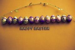 ανασκόπηση ζωηρόχρωμο Πάσχ&al Χρυσό κομφετί στα χρωματισμένα φύλλα Χρυσό αυγό Πάσχας στην επιφάνεια Τοπ άποψη των ρυθμίσεων ντεκό στοκ φωτογραφίες