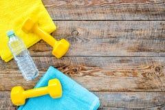 Ανασκόπηση ικανότητας Αλτήρες, πετσέτα και νερό στην ξύλινη τοπ άποψη υποβάθρου copyspace Στοκ φωτογραφία με δικαίωμα ελεύθερης χρήσης
