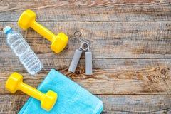 Ανασκόπηση ικανότητας Αλτήρες, πετσέτα και νερό στην ξύλινη τοπ άποψη υποβάθρου copyspace Στοκ Εικόνες