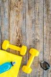 Ανασκόπηση ικανότητας Αλτήρες, πετσέτα και νερό στην ξύλινη τοπ άποψη υποβάθρου copyspace Στοκ εικόνα με δικαίωμα ελεύθερης χρήσης