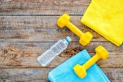 Ανασκόπηση ικανότητας Αλτήρες, πετσέτα και νερό στην ξύλινη τοπ άποψη υποβάθρου copyspace Στοκ φωτογραφίες με δικαίωμα ελεύθερης χρήσης