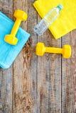 Ανασκόπηση ικανότητας Αλτήρες, πετσέτα και νερό στην ξύλινη τοπ άποψη υποβάθρου copyspace Στοκ Εικόνα