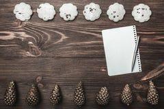 ανασκόπηση που επιβιβάζεται στο καφετί εσωτερικό δάσος τεμαχίων Τους χρυσούς κώνους και τα γλυκά μπισκότα που τακτοποιούνται με δ στοκ φωτογραφία