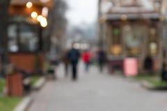 ανασκόπηση που θολώνεται αφηρημένη Unrecognizable σκιαγραφίες των ανθρώπων που περπατούν στην οδό πόλεων Στοκ Φωτογραφία