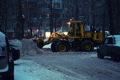 ανασκόπηση που θολώνεται Θαμπάδα φω'των πόλεων νύχτας Όχημα αφαίρεσης χιονιού που αφαιρεί το χιόνι στοκ φωτογραφία με δικαίωμα ελεύθερης χρήσης