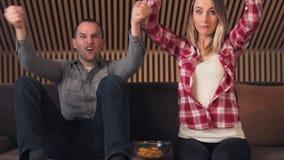 Ανατίναξη ζεύγους του παιχνιδιού ποδοσφαίρου προσοχής ευτυχίας στη TV απόθεμα βίντεο