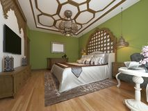 Ανατολική κρεβατοκάμαρα στο αραβικό ύφος, ξύλινο headboard και τους πράσινους τοίχους Μονάδα TV, πίνακας επιδέσμου, πολυθρόνα με  ελεύθερη απεικόνιση δικαιώματος