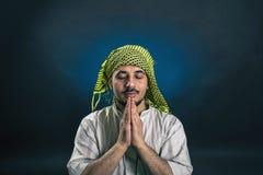 Ανατολικός-κοιτάζοντας άτομο στο παραδοσιακό, εθνικό αραβικό φόρεμα, προσεηθείτε με τα κλειστά μάτια και τα όπλα που διπλώνονται στοκ εικόνες