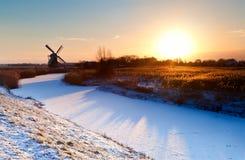 Ανατολή πέρα από τον ολλανδικό ανεμόμυλο και το παγωμένο κανάλι Στοκ Εικόνα