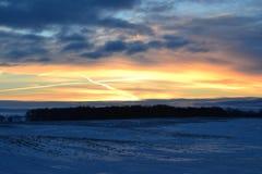 Ανατολή πέρα από το χιονώδη τομέα με τη διαγώνια μορφή στα σύννεφα Στοκ Φωτογραφία
