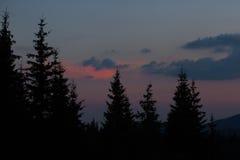 Ανατολή στα βουνά Οι περιλήψεις των κομψών κορυφών και των ακτίνων ήλιων ` s κάνουν τον τρόπο τους μέσω των αιχμών σύννεφων Υπόβα Στοκ Εικόνες