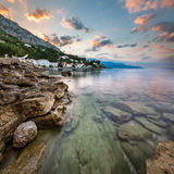Ανατολή στη δύσκολη παραλία και το μικρό χωριό κοντά σε Omis, Δαλματία Στοκ φωτογραφίες με δικαίωμα ελεύθερης χρήσης