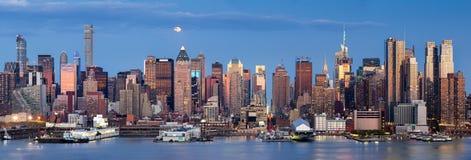 Ανατολή του φεγγαριού πέρα από την της περιφέρειας του κέντρου δύση με τον ορίζοντα του Μανχάταν, πόλη της Νέας Υόρκης Στοκ Εικόνες