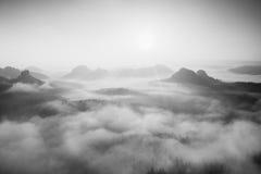 Ανατολή φθινοπώρου σε ένα όμορφο βουνό μέσα στην αντιστροφή Αιχμές των λόφων που αυξάνονται από το ομιχλώδες υπόβαθρο Γραπτή φωτο Στοκ Εικόνα