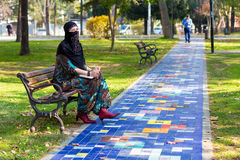 Ανατολική συνεδρίαση γυναικών στον πάγκο στη ζωηρόχρωμη αλέα πάρκων Στοκ Εικόνες
