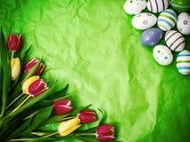 Ανατολικό αυγό, τουλίπες σε πράσινο τσαλακωμένο τυλίγοντας χαρτί Στοκ Φωτογραφία