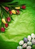 Ανατολικό αυγό, τουλίπες σε πράσινο τσαλακωμένο τυλίγοντας χαρτί Στοκ Εικόνες