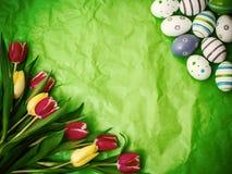 Ανατολικό αυγό, τουλίπες σε πράσινο τσαλακωμένο τυλίγοντας χαρτί Στοκ φωτογραφία με δικαίωμα ελεύθερης χρήσης