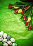 Ανατολικό αυγό, τουλίπες σε πράσινο τσαλακωμένο τυλίγοντας χαρτί Στοκ Φωτογραφίες