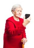 Ανατρέψτε την ηλικιωμένη γυναίκα χρησιμοποιώντας την οθόνη αφής κινητή Στοκ εικόνες με δικαίωμα ελεύθερης χρήσης