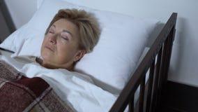 Ανατρέψτε την ώριμη γυναίκα στο νοσοκομειακό κρεβάτι, που ενοχλείται με τη αθεράπευτη υγεία ασθενειών απόθεμα βίντεο