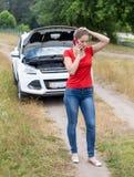 Ανατρέψτε τη νέα γυναίκα έσπασε το αυτοκίνητο στον τομέα και την απαίτηση της βοήθειας Στοκ Εικόνες