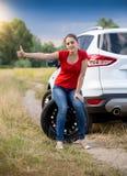 Ανατρέψτε τη νέα γυναίκα με το σπασμένο αυτοκίνητο στον εγκαταλειμμένο δρόμο που κάνει ωτοστόπ και που περιμένει τη βοήθεια Στοκ εικόνα με δικαίωμα ελεύθερης χρήσης