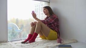 Ανατρέψτε το ενήλικο όμορφο κοίταγμα γυναικών μέσω του παραθύρου απόθεμα βίντεο