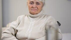 Ανατρέψτε το ηλικιωμένο θηλυκό που εξετάζει τα χάπια και το ποτήρι του νερού, εξάρτηση φαρμάκων απόθεμα βίντεο