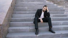 Ανατρέψτε το νέο επιχειρησιακό άτομο που έχει την πίεση και που κάθεται στα σκαλοπάτια στην οδό Επιχειρηματίας που έχει την έννοι στοκ φωτογραφίες με δικαίωμα ελεύθερης χρήσης