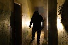 Ανατριχιαστική σκιαγραφία με το μαχαίρι στην εγκαταλειμμένη σκοτάδι οικοδόμηση Φρίκη για τη μανιακή έννοια στοκ εικόνες