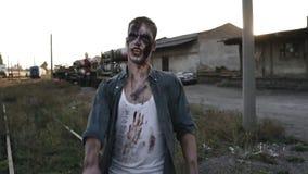 Ανατριχιαστικό άτομο zombie στα αιματηρά ενδύματα που περπατά από τις γραμμές σιδηροδρόμων υπαίθρια με μια βιομηχανική εγκαταλειμ απόθεμα βίντεο