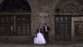 Ανατριχιαστικό ζεύγος σε ένα γαμήλιο φόρεμα με το makeup για τη στάση αποκριών κοντά στο τουβλότοιχο απόθεμα βίντεο