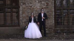 Ανατριχιαστικό ζεύγος σε ένα γαμήλιο φόρεμα με το makeup για τη στάση αποκριών κοντά στο τουβλότοιχο φιλμ μικρού μήκους