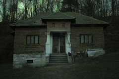 Ανατριχιαστικό συχνασμένο σπίτι με τη σκοτεινή ατμόσφαιρα φρίκης Μια μαύρες γάτα και μια πανσέληνος πίσω από τη frightful σκηνή στοκ φωτογραφία με δικαίωμα ελεύθερης χρήσης