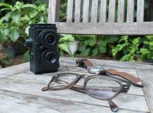 Αναδρομικά κάμερα, eyeglasses και ρολόι στο ξύλινο υπόβαθρο στοκ φωτογραφία