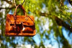 Αναδρομικά καφετιά τσάντα και σημειωματάριο δέρματος ατόμων στη φωτεινή ζωηρόχρωμη θερινή χλόη Στοκ Εικόνες