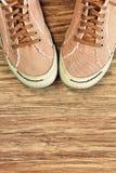Αναδρομικά παπούτσια γυμναστικής ύφους στο ξύλινο υπόβαθρο με το κενό διάστημα Στοκ εικόνα με δικαίωμα ελεύθερης χρήσης