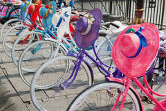 Αναδρομικά παλαιά ζωηρόχρωμα ποδήλατα σχεδίου με τα καπέλα και τα κράνη γυναικών στοκ φωτογραφία