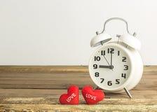 Αναδρομικές ρολόι και καρδιές στο ξύλινο και άσπρο υπόβαθρο Στοκ Εικόνα