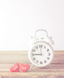 Αναδρομικές ρολόι και καρδιές στο ξύλινο και άσπρο υπόβαθρο Στοκ εικόνα με δικαίωμα ελεύθερης χρήσης