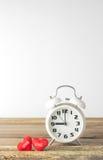 Αναδρομικές ρολόι και καρδιές στο ξύλινο και άσπρο υπόβαθρο Στοκ Φωτογραφίες