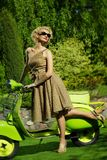 Αναδρομική γυναίκα υπαίθρια με ένα πράσινο μηχανικό δίκυκλο Στοκ Εικόνα